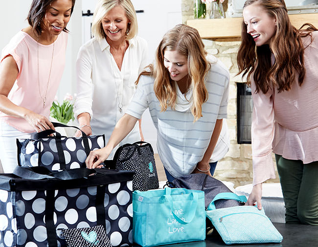 Host and guests looking at Thirty-One bags